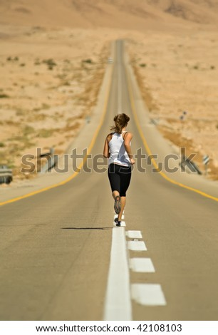 Young girl running over a desert highway. - stock photo
