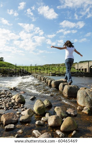 Young girl runs across stepping stones  to cross a stream - stock photo