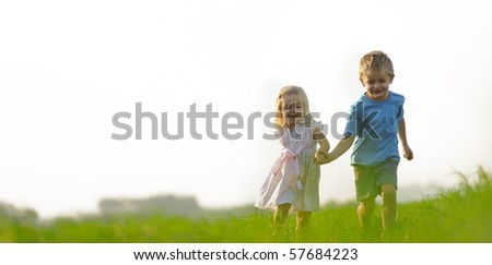 Young girl runs through a field, happy and having fun. - stock photo