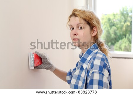 Young girl  sanding wall in her home
