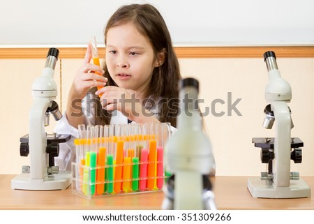 Young girl scientist with microscope holding test tubes in science lab
