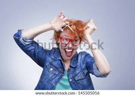 young girl screams and cuts her hair with scissors with mad eyes. Bad day at the hairdresser. Studio shot. Gray background - stock photo