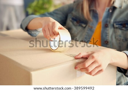 Young girl sealing with tape big cardboard box for moving - stock photo
