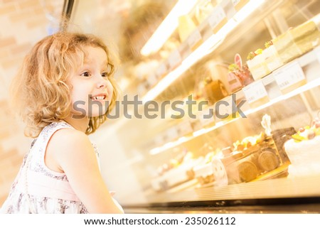 Young girl selection of cakes in the bakery section of a supermarket - stock photo