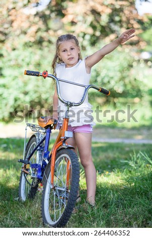 Young girl seven years standing with bicycle in the park - stock photo