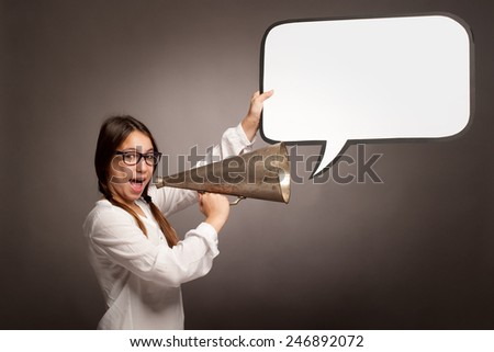 young girl shouting with an old megaphone on a gray background - stock photo