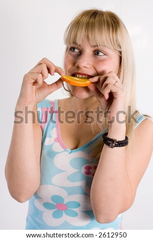 Young girl show and eating a piece of orange