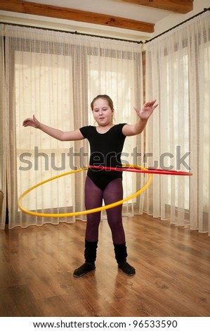 Young girl show gymnastics dance with hoop at home