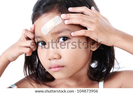 Young girl showing a wound plaster in her head. - stock photo