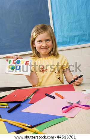 Young girl showing card made in art class that says I love you. - stock photo