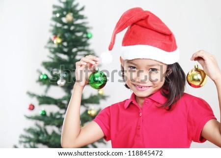 Young girl showing christmas balls for christmas tree - stock photo