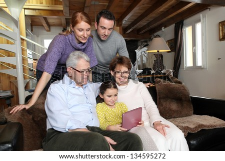 Young girl showing her family her laptop - stock photo