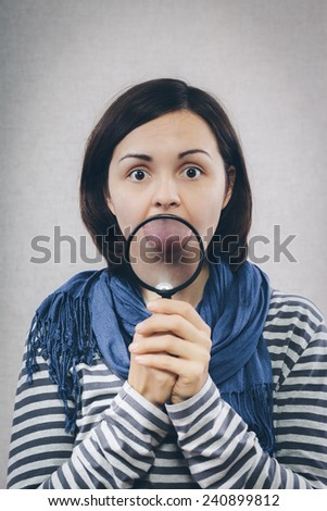 young girl showing her mouth through a magnifying glass - stock photo