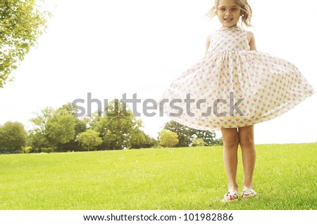 Young girl showing off her dress and wearing pink shades in the park. - stock photo