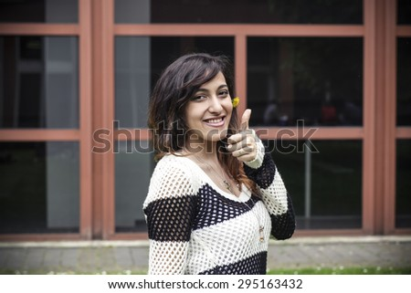 Young girl showing thumb up gesture - stock photo