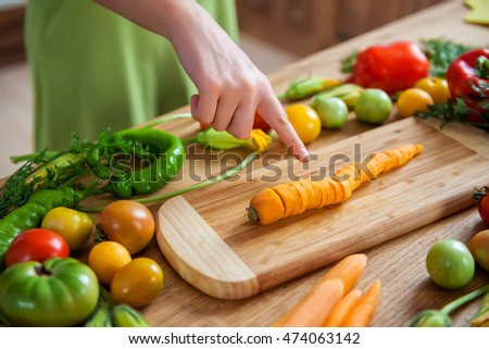 young girl shows cut into slices juicy fresh bright carrots folded marvelous pieces on wooden cutting board surface is surrounded by a crop of organic vegetables, tomato, pepper and zucchini flowers