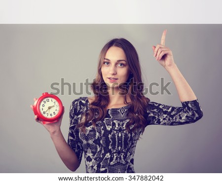 Young girl shows up at a place for inscriptions. Girl student or office worker holding a clock. It's time to take a break to rest. Pointing at the sign for text. Happy latin woman pointing on a clock. - stock photo