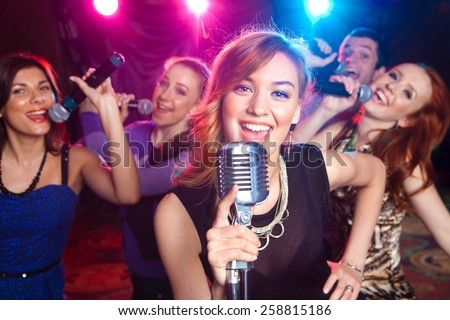 Young girl singing into  microphone at  party - stock photo