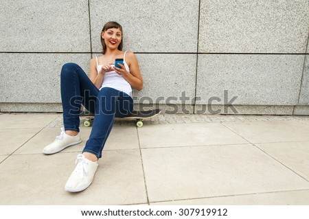 Young girl siting on skateboard in the city with phone by the wall, smiling. - stock photo