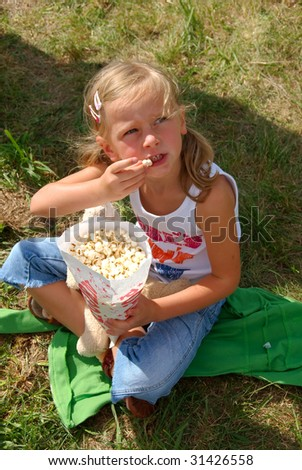 Young girl siting on the grass and eats popcorn. - stock photo