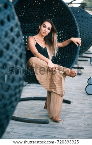 Elegant Young Girl Sits On A Terrace In A Wooden Round Chair. The Model Enjoys A