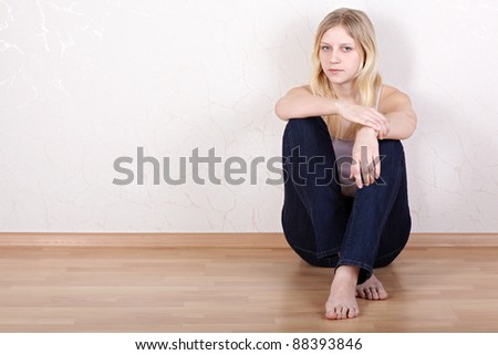 Young girl sits on the floor with her back pressed against the wall. - stock photo