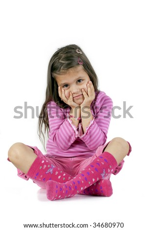 young girl sits with her legs crossed and hands on Face. - stock photo
