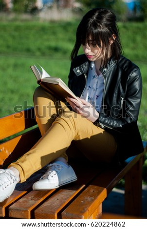 Young girl sitting and reading a book on a sunny and beautiful spring day in the park on a bench