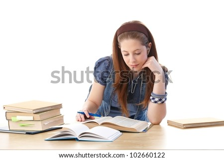 Young girl sitting at desk at home, doing homework, looking at books. - stock photo
