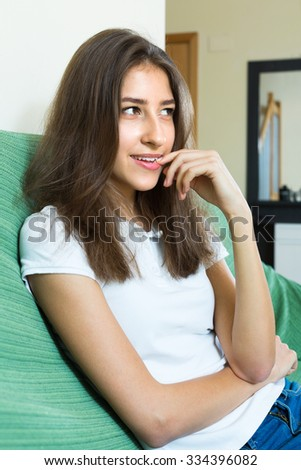 Young girl sitting at sofa and biting nails indoors