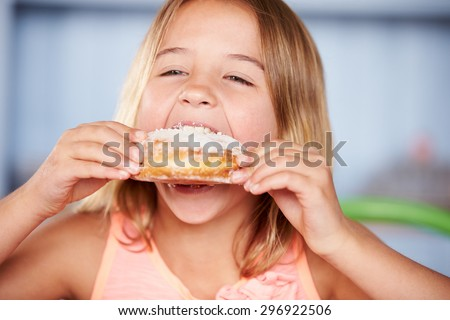 Young Girl Sitting At Table Eating Sugary Donut