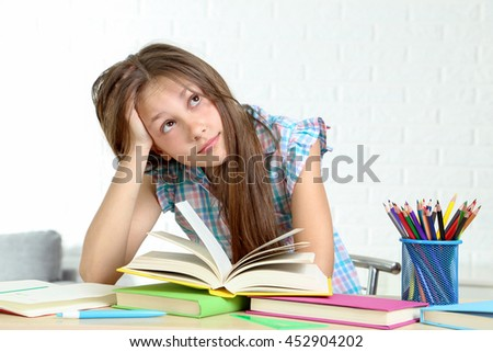 Young girl sitting at the desk and reading book - stock photo