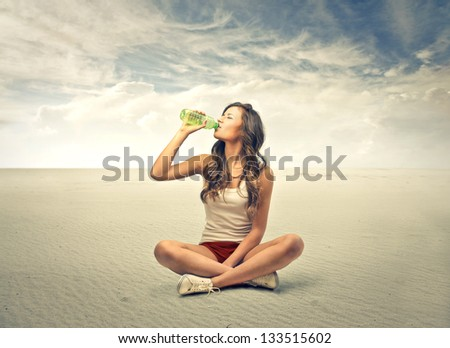 young girl sitting cross-legged drinking water from bottle in the desert - stock photo