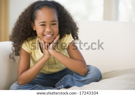 Young Girl Sitting Cross Legged On A Sofa At Home - stock photo
