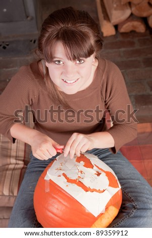 young girl sitting down concentrated carving a pumpkin for halloween