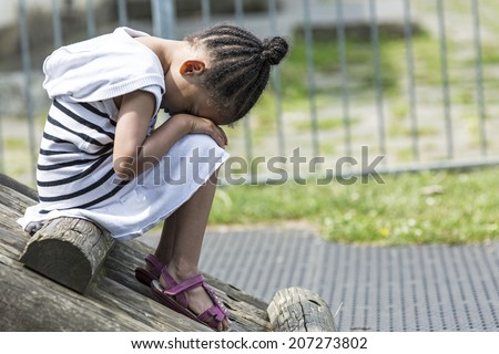 Young girl sitting in a playground in the day with her face in her lap because she is sad - stock photo