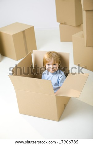 Young girl sitting in cardboard box between other boxes. She's smiling and looking at camera.