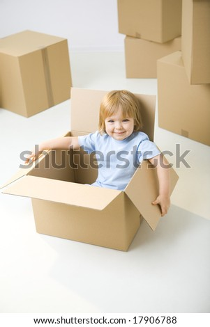 Young girl sitting in cardboard box between other boxes. She's smiling and looking at camera. - stock photo