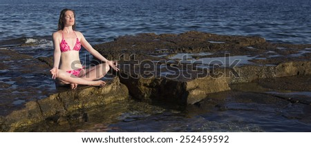 Young girl sitting in front of sea and meditating - stock photo