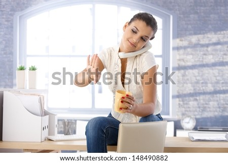 Young girl sitting in office, talking on landline phone, looking at nails, drinking tea. - stock photo