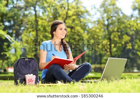 Young girl sitting in park and writing in notebook