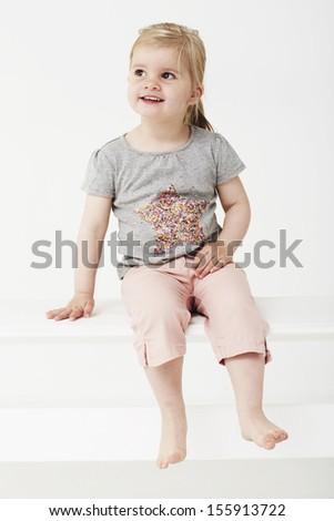 Young girl sitting in studio - stock photo