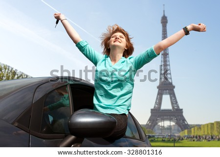 young girl sitting in the car and holding a key against blue sky in Paris, France, next to Eiffel tower - stock photo
