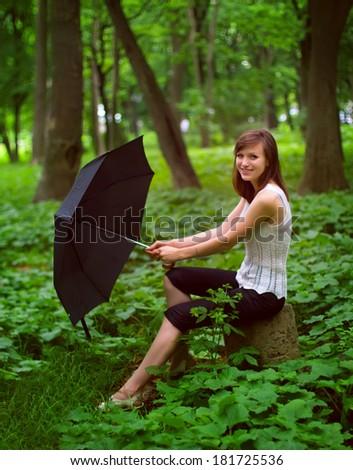 Young girl sitting in the park with umbrella