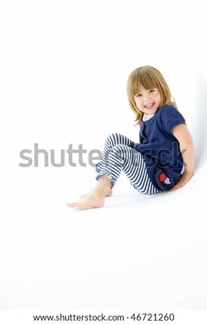 Young Girl Sitting In WhiteStudio - stock photo