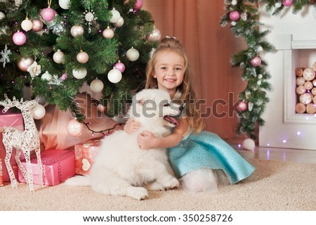 Young girl sitting near Christmas tree and gift box and hug white puppy. New Year. - stock photo