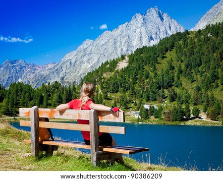 Young girl sitting on a bench near the lake in the mountain - stock photo
