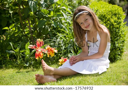 Young girl sitting on a field with flowers - stock photo