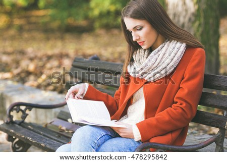 Young girl sitting on a park bench and reading a book, on a beautiful autumn day