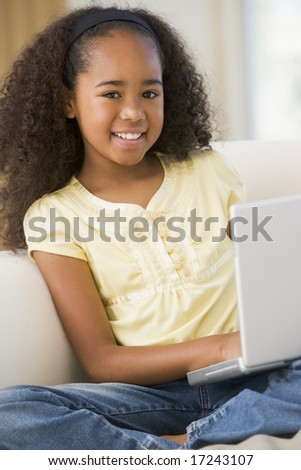 Young Girl Sitting On A Sofa, Using A Laptop - stock photo